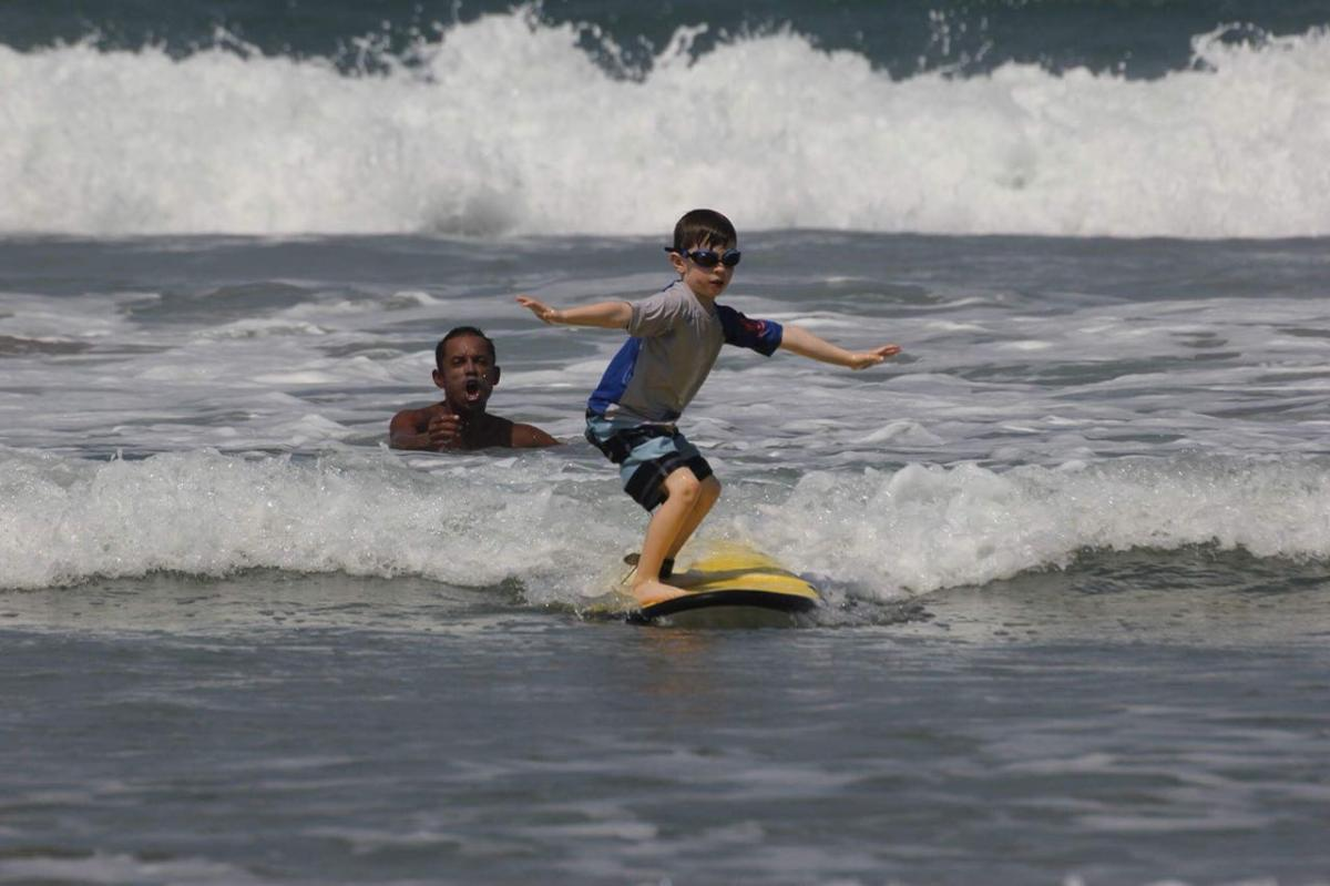 Young boy learning to surf in Tamarindo Costa Rica